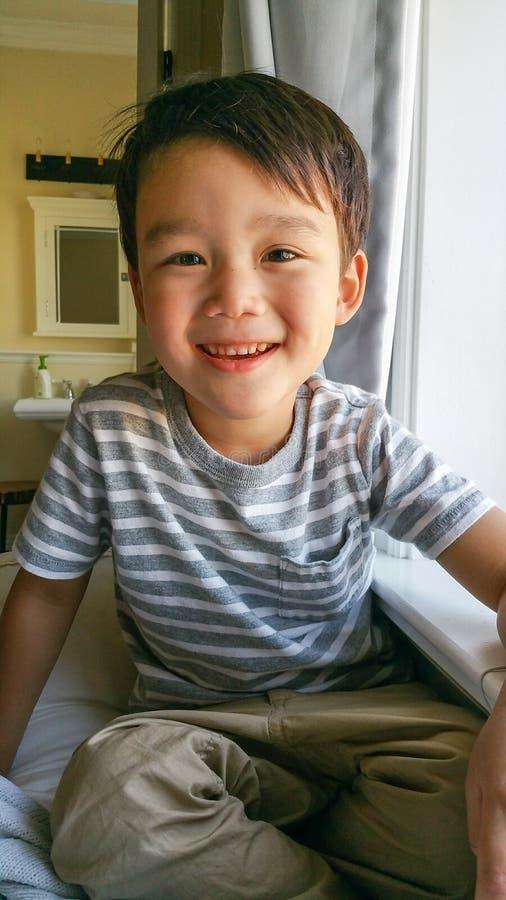 Muchacho chino y caucásico joven lindo feliz que se sienta cerca de ventana foto de archivo libre de regalías