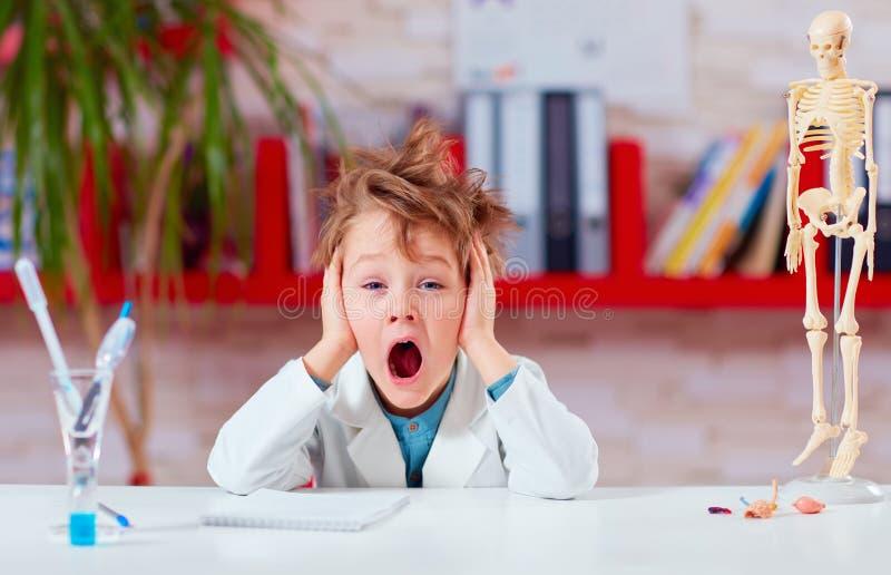 Muchacho, colegial que bosteza durante el experimento en laboratorio de la escuela foto de archivo