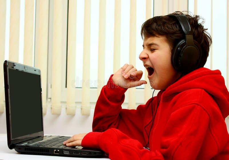 Muchacho con bostezo de la computadora portátil foto de archivo libre de regalías