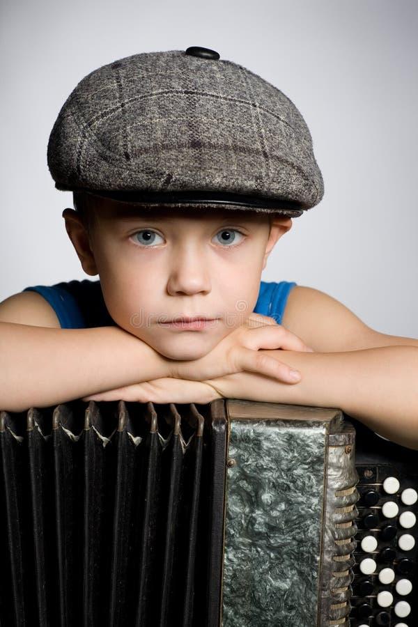 Muchacho con el acordión. imagenes de archivo
