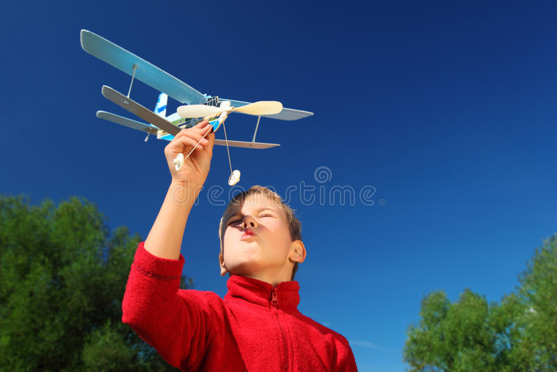 Muchacho con el aeroplano del juguete en las manos al aire libre fotos de archivo libres de regalías