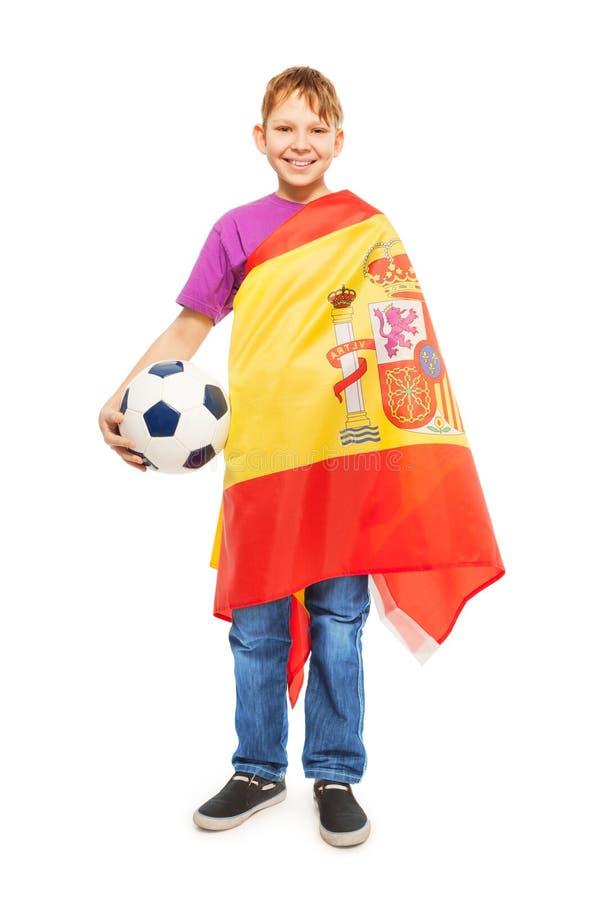 Muchacho con el balón de fútbol envuelto en una bandera española fotos de archivo