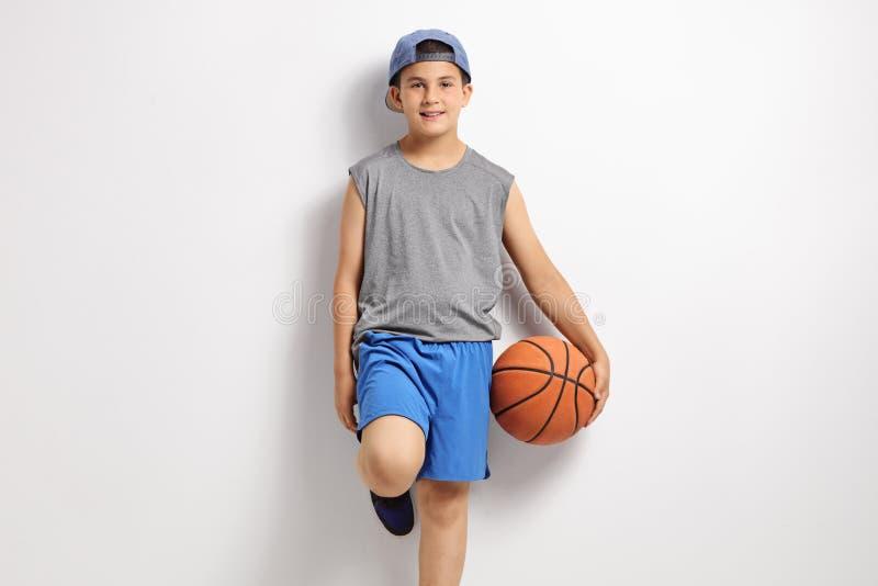Muchacho con el baloncesto que se inclina contra una pared imágenes de archivo libres de regalías
