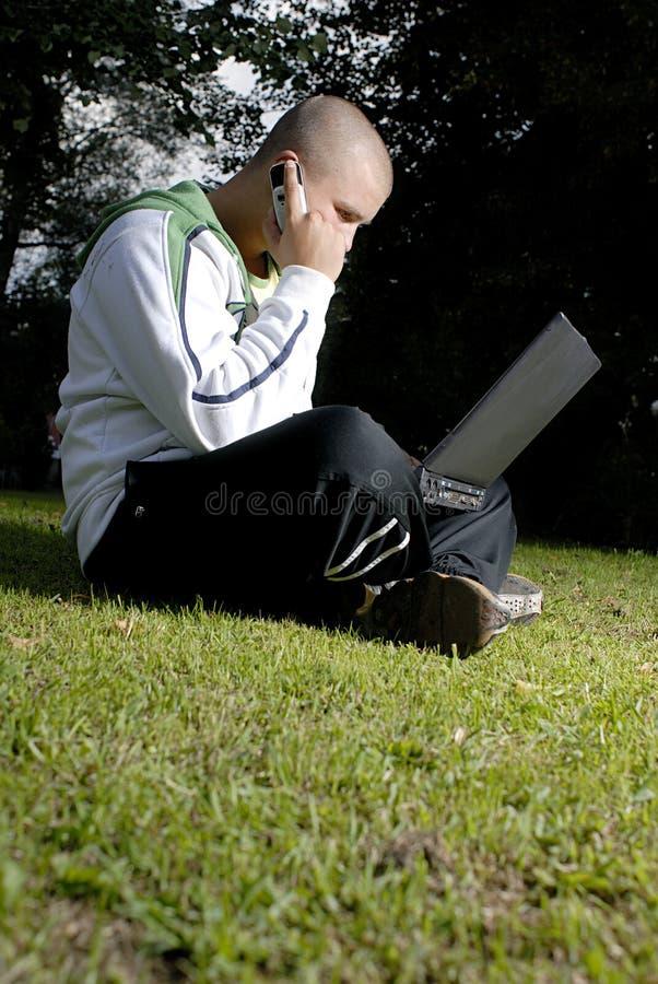 Muchacho con el cuaderno y el teléfono celular en parque fotografía de archivo