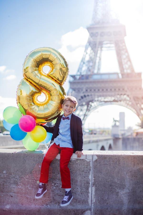 Muchacho con el manojo de globos coloridos en París cerca de la torre Eiffel fotos de archivo