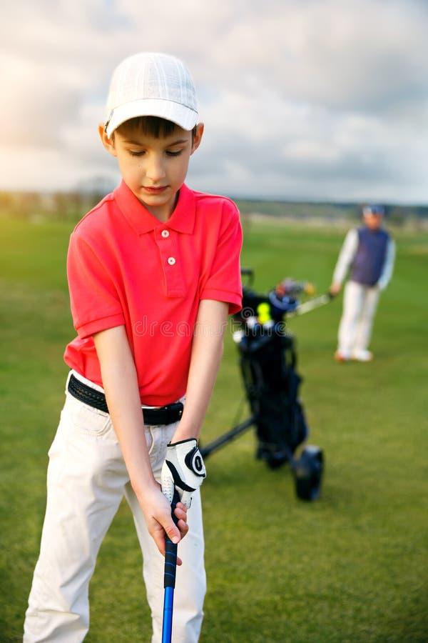 Muchacho con el padre en el golf fotografía de archivo
