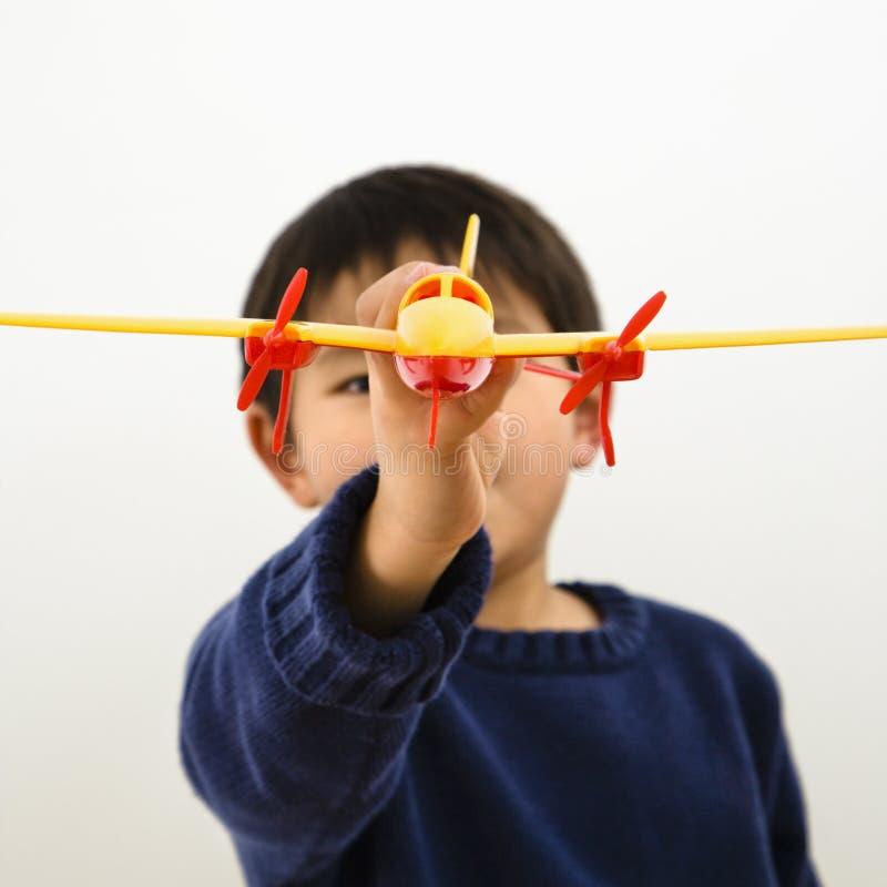 Muchacho con el plano del juguete foto de archivo