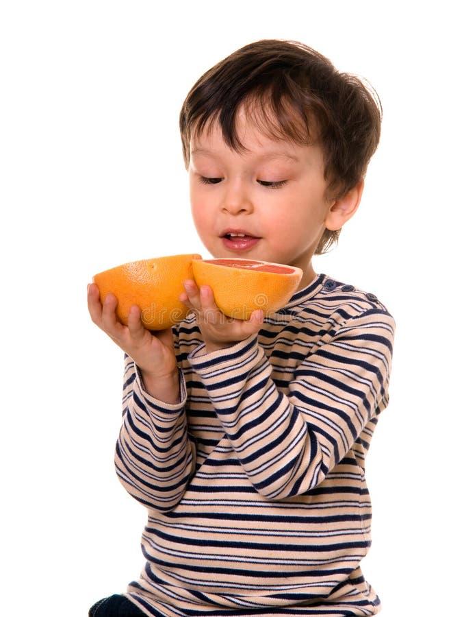 Muchacho con el pomelo. imagen de archivo