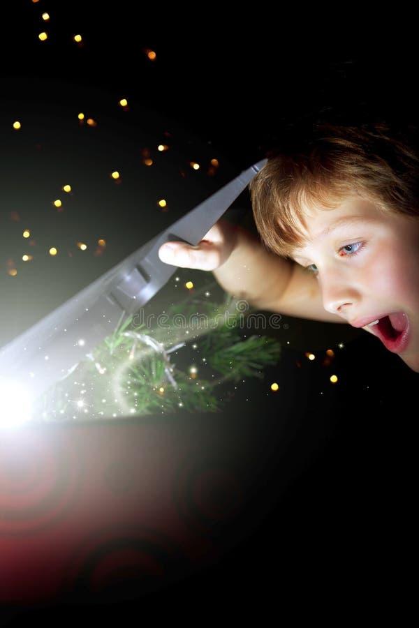 Muchacho con el regalo de la Navidad sobre obscuridad imagen de archivo libre de regalías