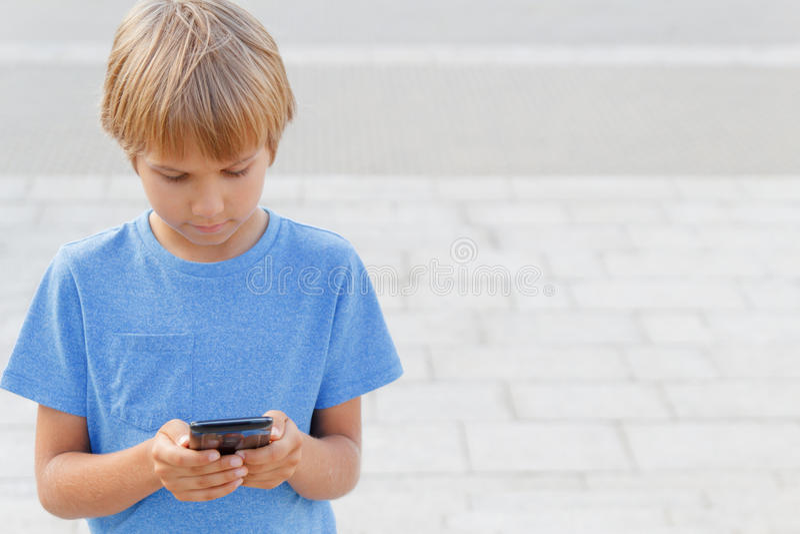 Muchacho con el teléfono móvil en la calle Niño que mira la pantalla, jugando a juegos, usando apps Fondo de la ciudad Escuela imágenes de archivo libres de regalías