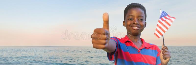 Muchacho con la bandera americana que da los pulgares para arriba contra el agua y que iguala el cielo fotografía de archivo libre de regalías