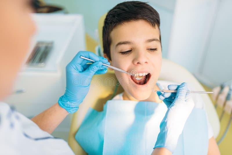 Muchacho con la boca abierta en una silla dental imagen de archivo