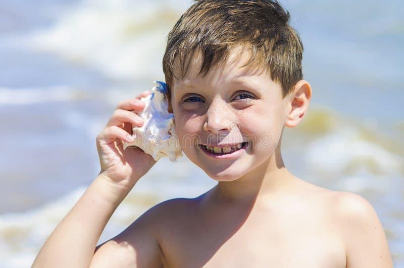 Muchacho con la cáscara a disposición en la playa imagenes de archivo