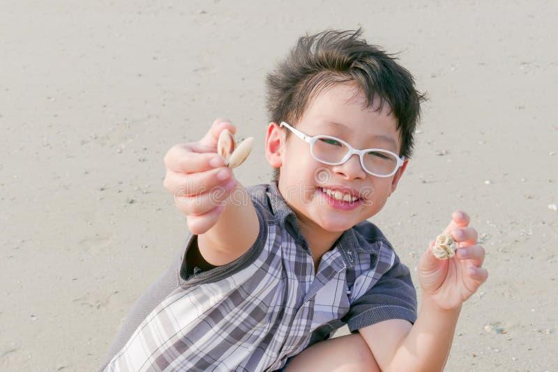 Muchacho con la cáscara en la playa fotografía de archivo