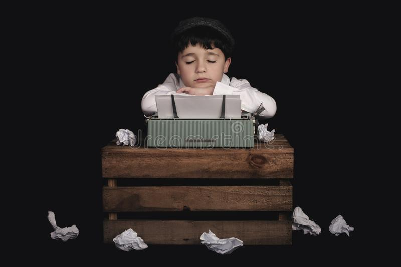Muchacho con la máquina de escribir vieja fotografía de archivo