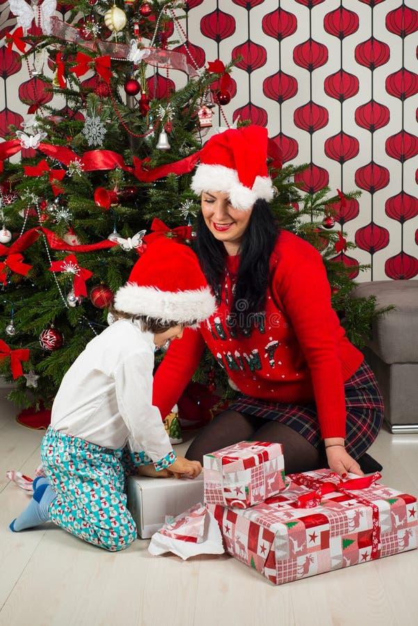 Muchacho con la madre que abre los regalos de Navidad foto de archivo libre de regalías