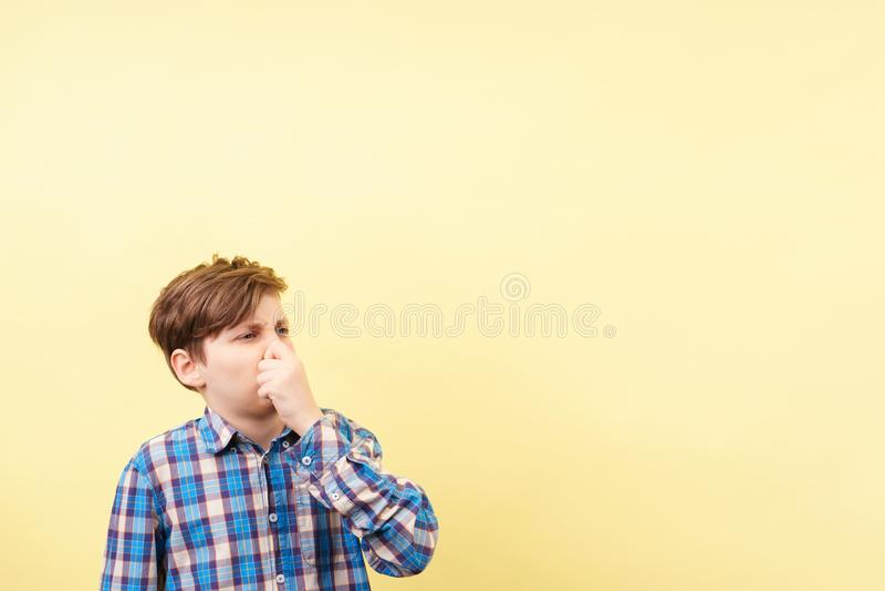 Muchacho con la nariz asqueada de la cubierta de la expresión de la cara fotografía de archivo libre de regalías