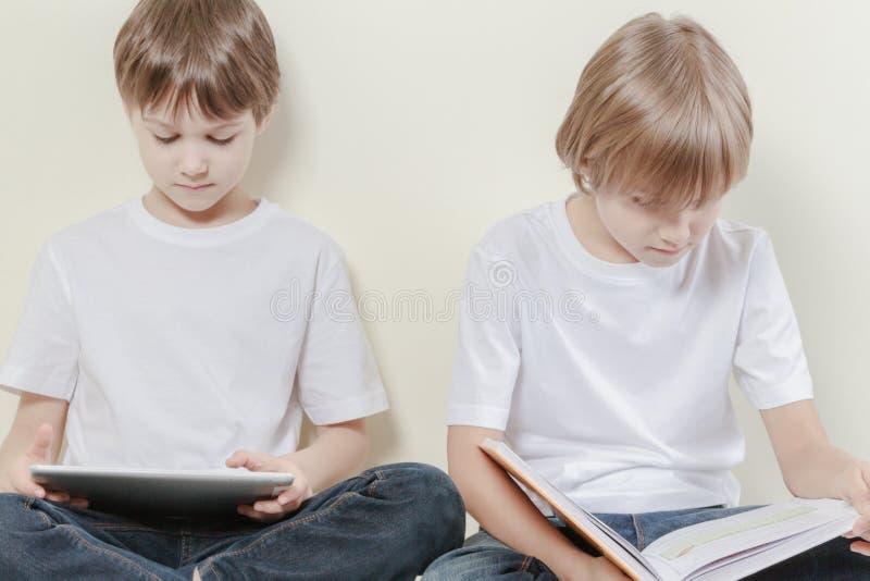 Muchacho con la tableta y el niño que leen un libro Embroma concepto del ocio de la educación imagenes de archivo