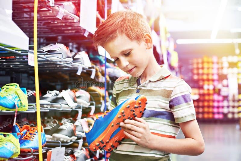 Muchacho con las botas del fútbol en tienda del deporte imagenes de archivo