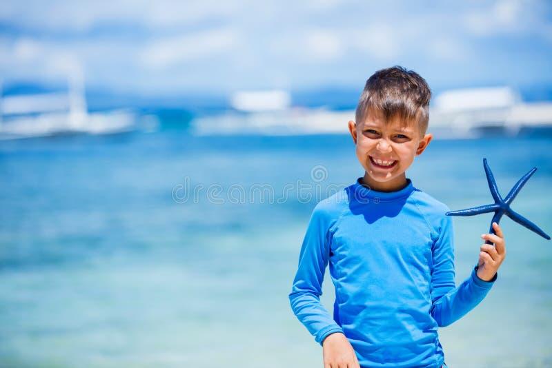 Muchacho con las estrellas de mar foto de archivo