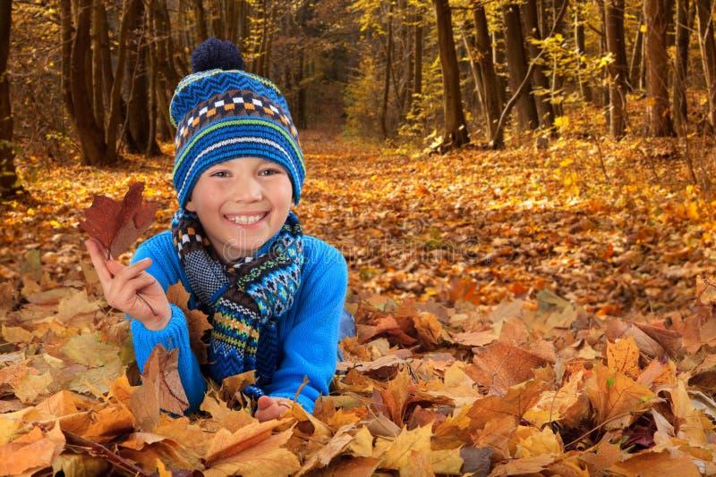 Muchacho con las hojas de otoño imagen de archivo libre de regalías