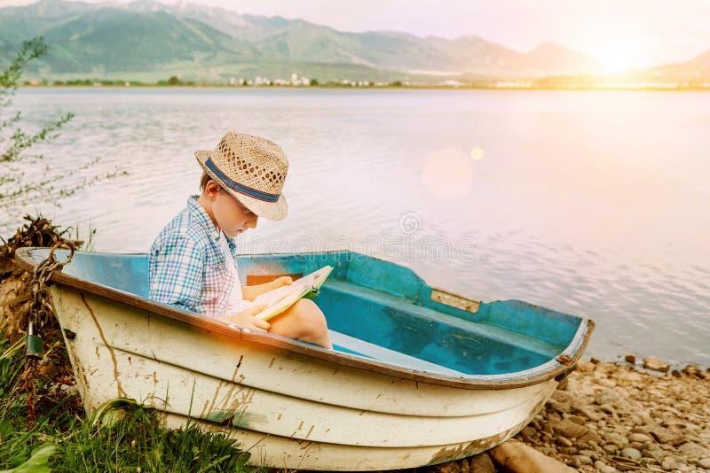 Muchacho con los asientos del libro en barco viejo en el banco del lago fotos de archivo libres de regalías