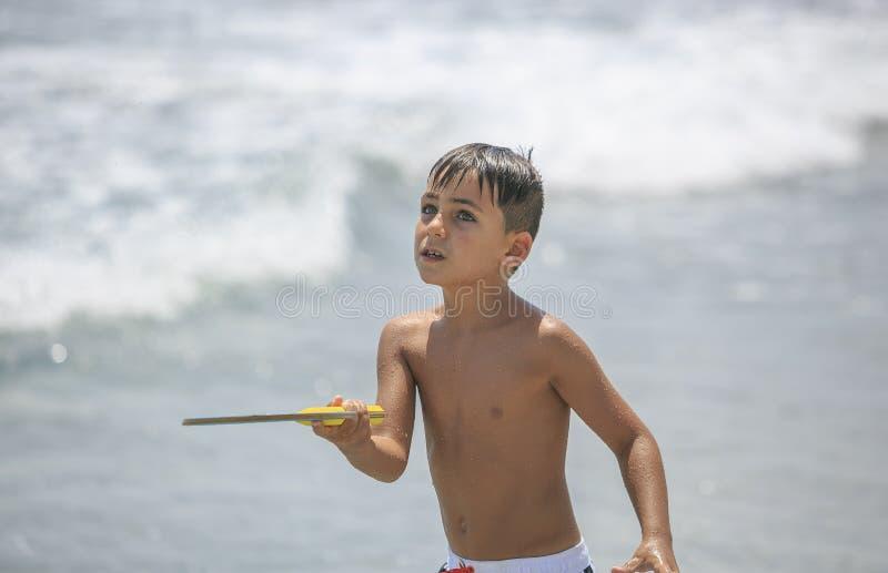 Muchacho con los ojos verdes que juegan a tenis en la playa imágenes de archivo libres de regalías