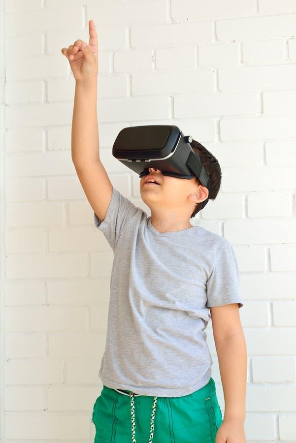 Muchacho con los vidrios de la realidad virtual en fondo de la pared de ladrillo imagenes de archivo