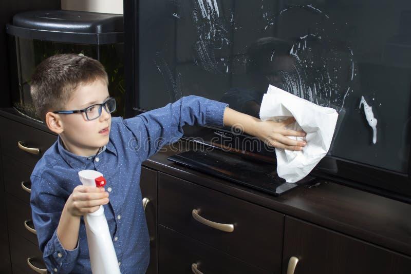 Muchacho con los vidrios durante la limpieza Él limpia la pantalla de la TV con polvo del paño imágenes de archivo libres de regalías