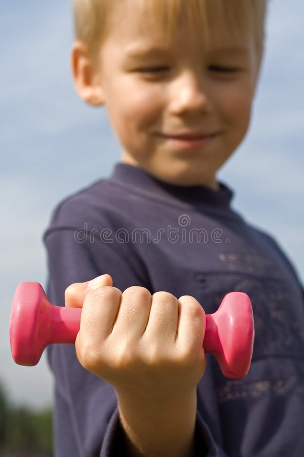 Muchacho con pesa de gimnasia imagen de archivo