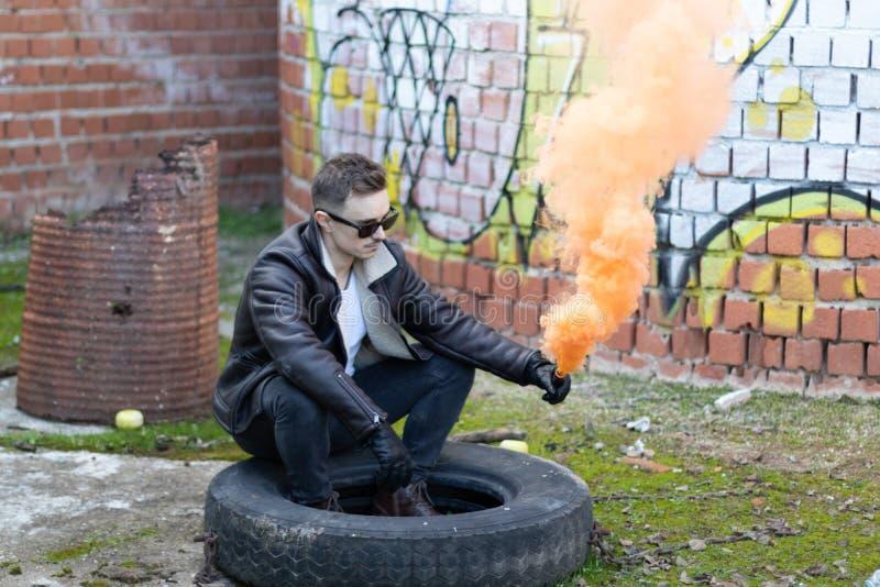 Muchacho con ropa y gafas de sol modernas con una llamarada del humo en un lugar abandonado fotos de archivo