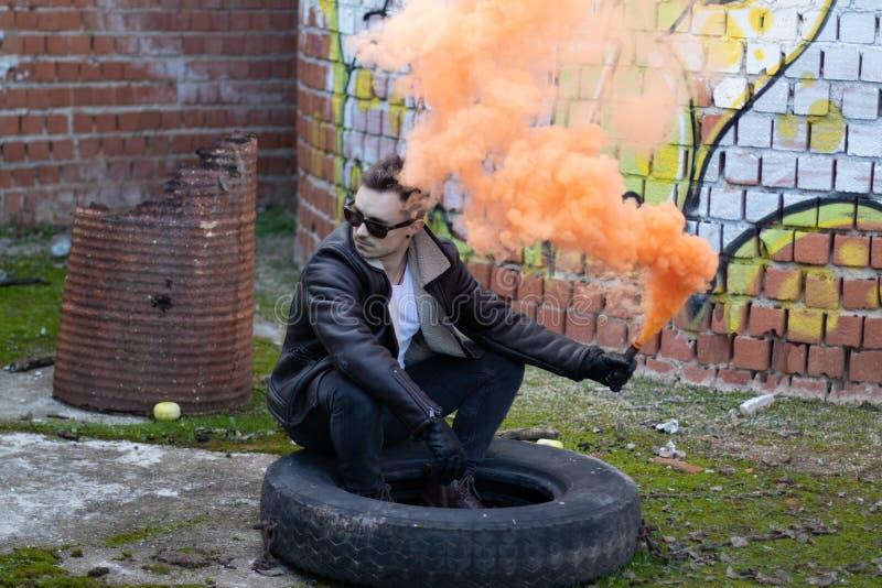 Muchacho con ropa y gafas de sol modernas con una llamarada del humo en un lugar abandonado foto de archivo