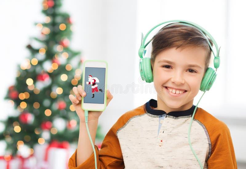 Muchacho con smartphone y auriculares en la Navidad imágenes de archivo libres de regalías