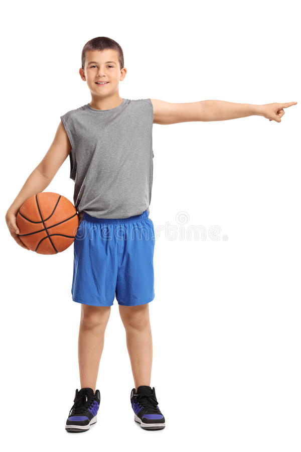 Muchacho con un baloncesto que señala a la derecha imagen de archivo