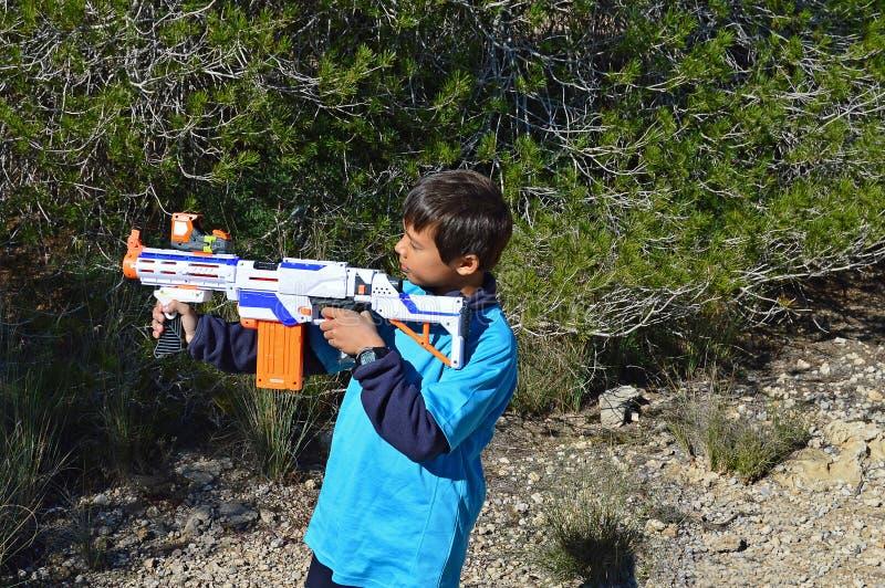 Muchacho con un rifle plástico imagen de archivo