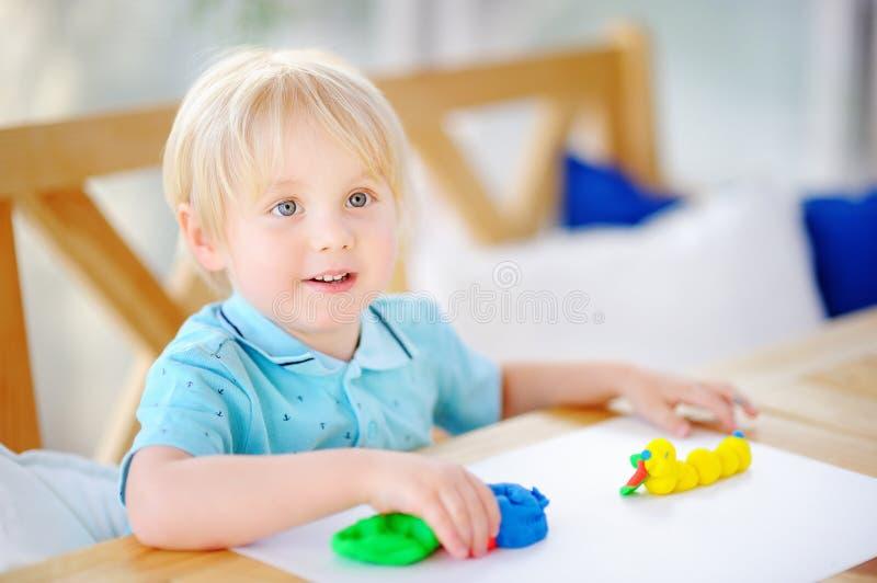 Muchacho creativo que juega con la arcilla de modelado colorida en la guardería fotografía de archivo libre de regalías