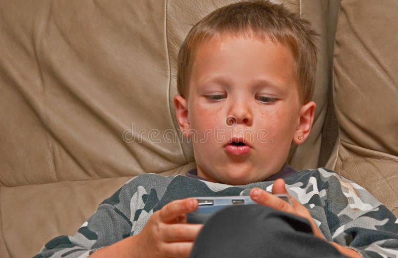 Muchacho de 5 años con las pecas que juegan al juego video fotografía de archivo libre de regalías