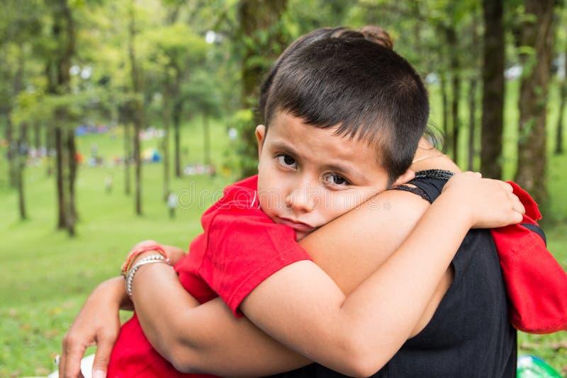 Muchacho de 8 años que abraza a su madre en el parque y que mira la cámara con la expresión emocional en su cara fotografía de archivo
