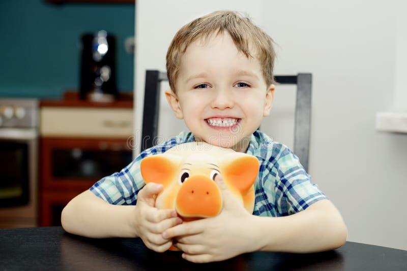 Muchacho de 4 años que sonríe mientras que sostiene una hucha imagen de archivo