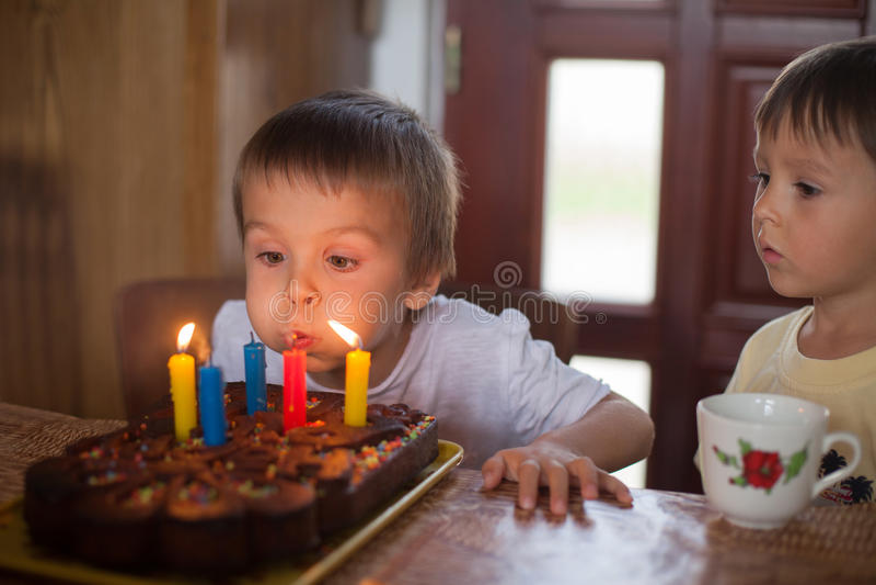 Muchacho de cinco años adorable que celebra su cumpleaños y soplar fotografía de archivo