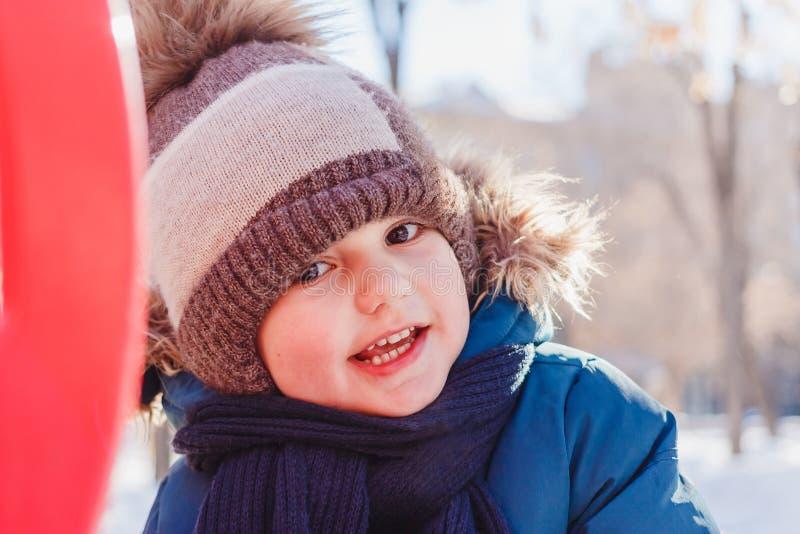 Muchacho de cuatro años en un paseo en invierno fotos de archivo