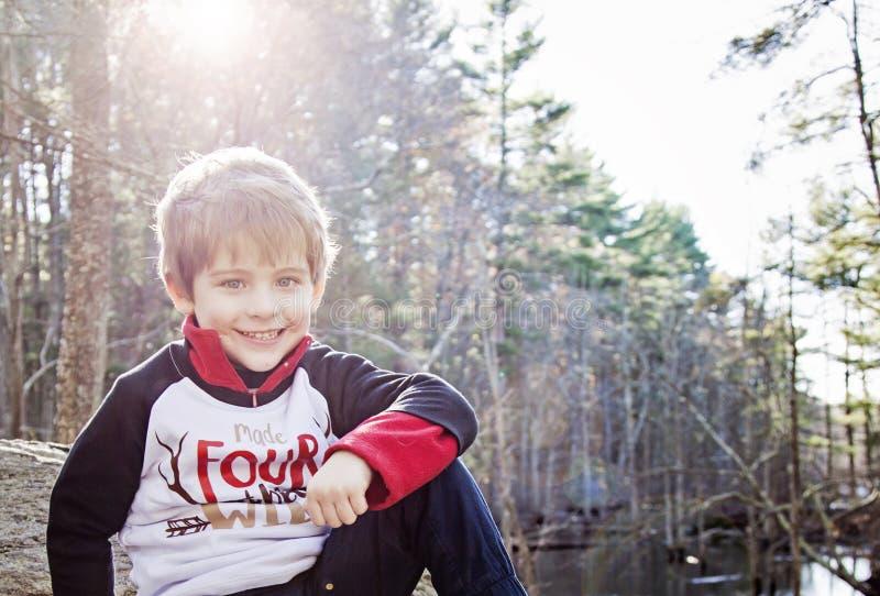 Muchacho de cuatro años feliz que se sienta en bosque afuera foto de archivo