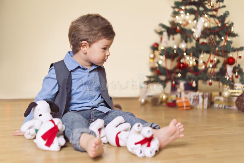 Muchacho de dos años con el árbol de navidad y los juguetes imagen de archivo libre de regalías