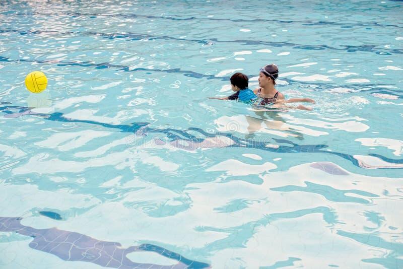 Muchacho de dos años en la primera lección de la natación con su madre imagenes de archivo