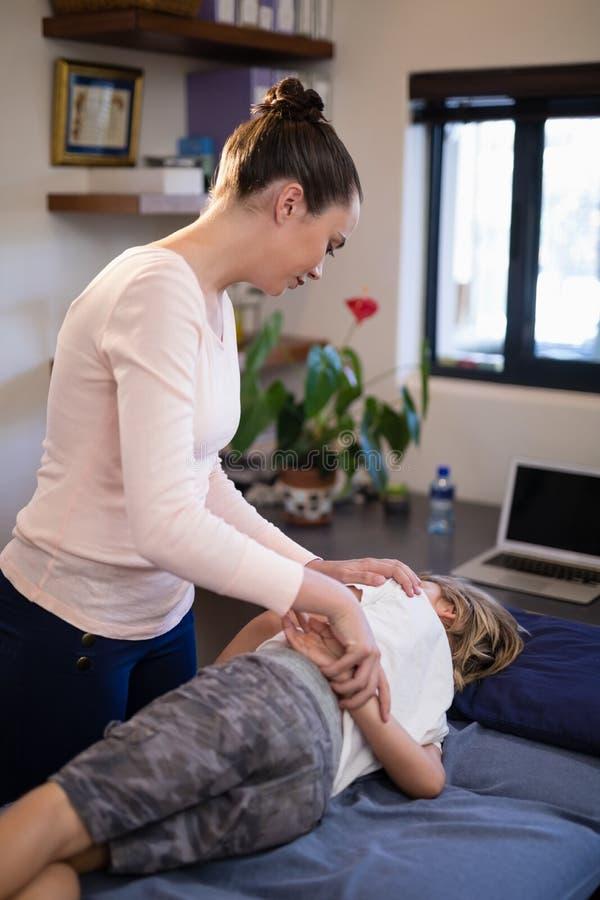 Muchacho de examen del terapeuta de sexo femenino joven que miente en cama fotos de archivo