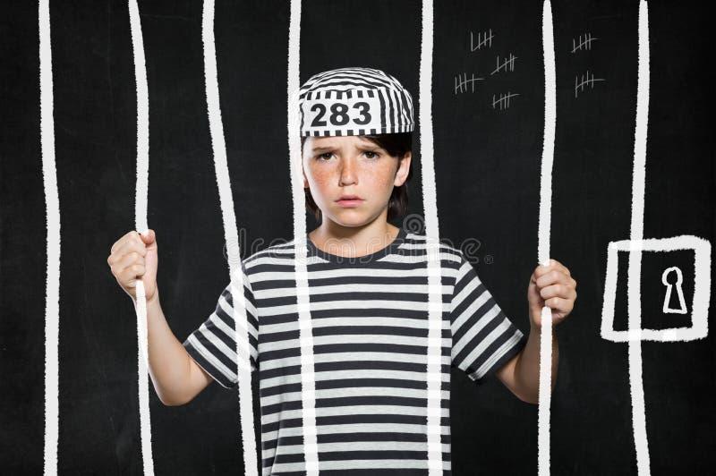 Muchacho de la broma en cárcel foto de archivo