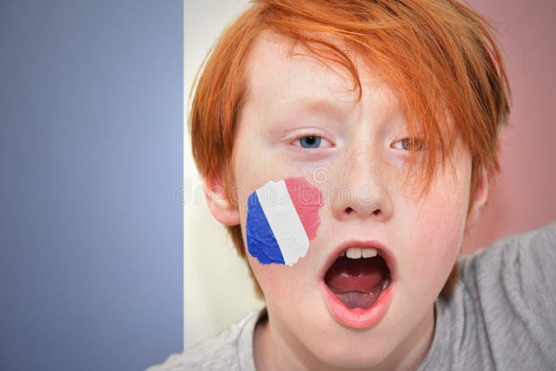 Muchacho de la fan del pelirrojo con la bandera francesa pintada en su cara imágenes de archivo libres de regalías