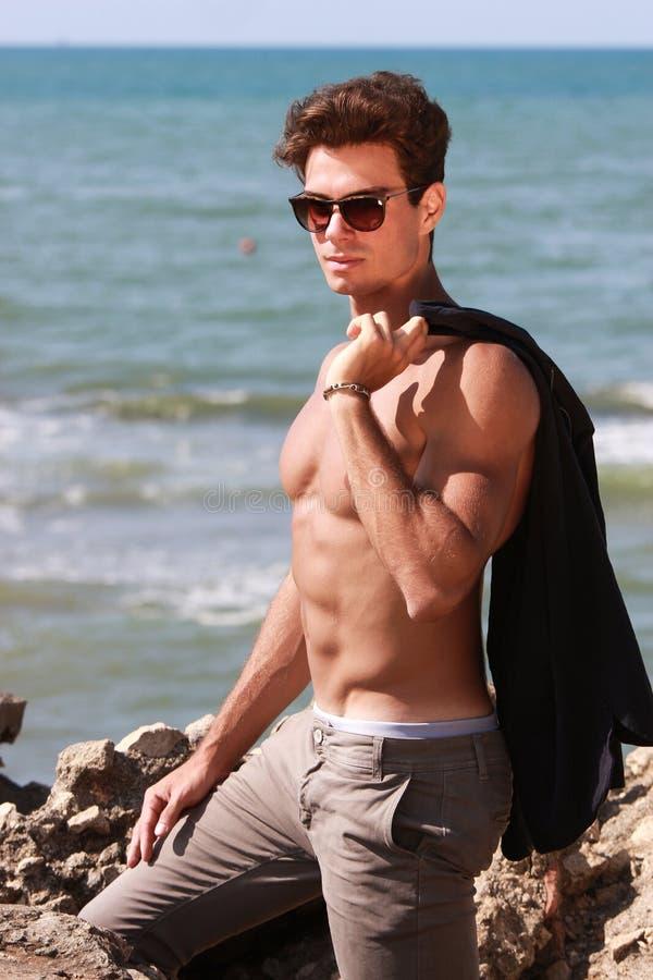 Muchacho de la moda de los jóvenes que presenta en el mar cerca de la roca shirtless foto de archivo libre de regalías