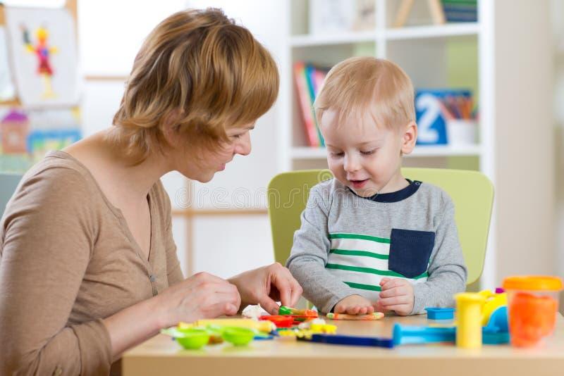 Muchacho de la mujer y del niño que juega con plasticine en la tabla en sitio del cuarto de niños imágenes de archivo libres de regalías