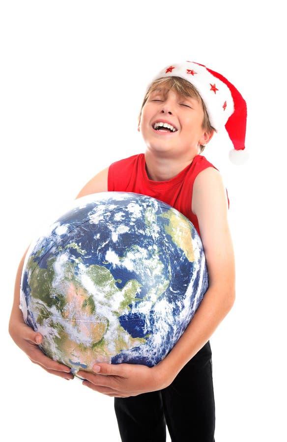 Muchacho de la Navidad que abraza la tierra del planeta fotos de archivo libres de regalías
